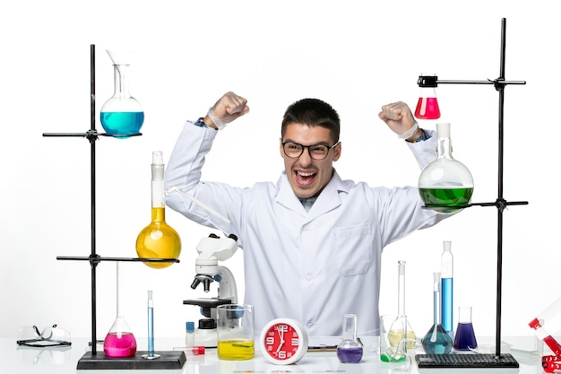 Front view male chemist in white medical suit sitting with solutions rejoicing on white background virus science covid pandemic lab