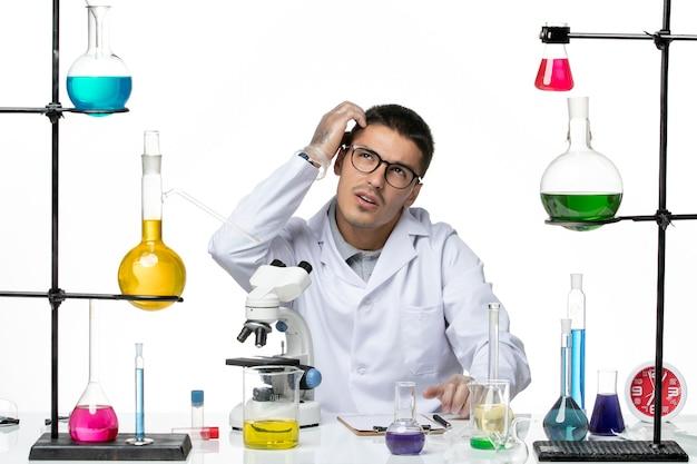 Chimico maschio di vista frontale in vestito medico bianco che si siede con soluzioni pensando su sfondo bianco virus lab covid-malattia scienza