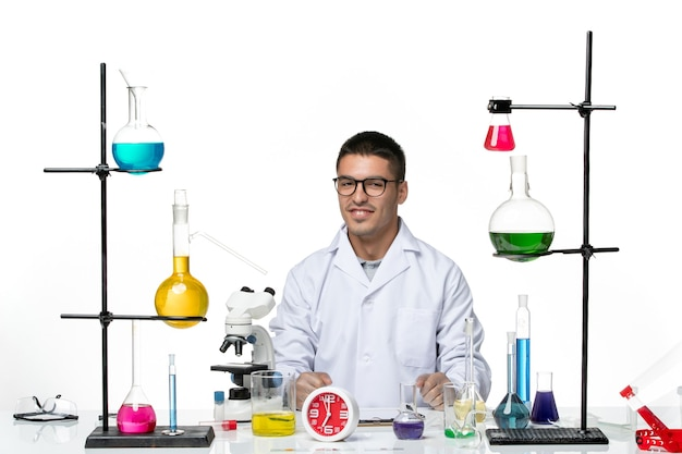 Front view male chemist in white medical suit sitting with solutions on white background virus science covid pandemic lab
