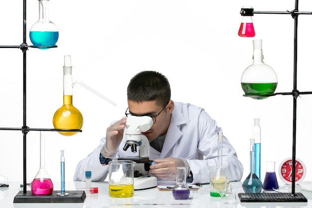 Front view male chemist in white medical suit using microscope on a white background virus lab covid- disease science