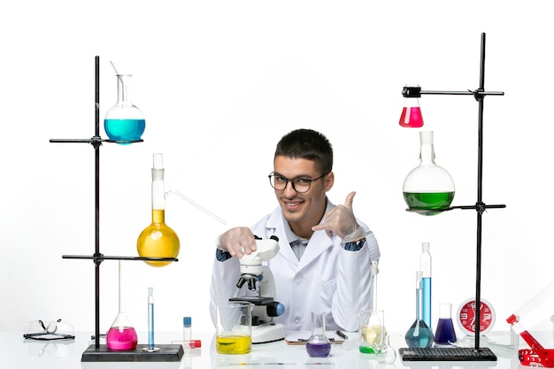 Front view male chemist in white medical suit using microscope with smile on white background virus covid- disease lab science