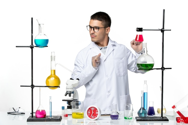 Front view male chemist in white medical suit working with solutions on a white background science covid- lab pandemic virus