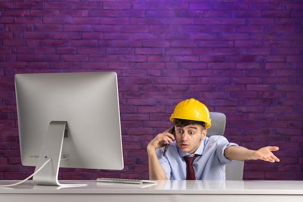 Вид спереди мужской конструктор за офисным столом разговаривает по телефону