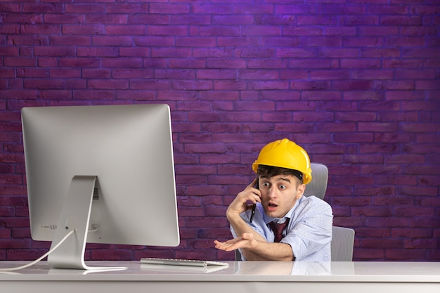 Front view male constructor behind office desk talking at phone