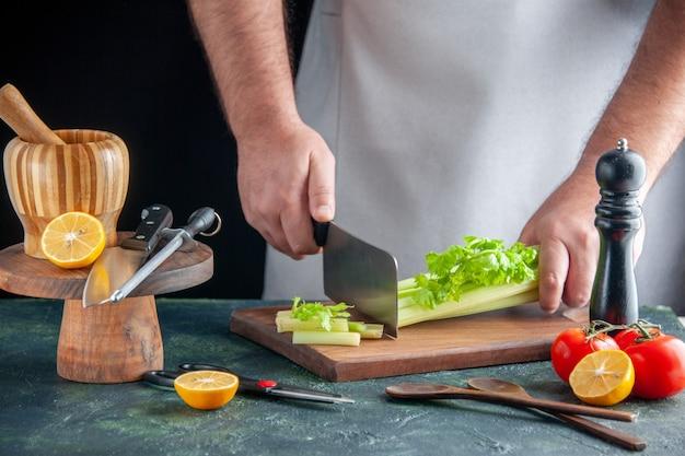 Вид спереди мужского повара, режущего сельдерей на темной стене, салат, диетическое питание, цветное фото, здоровье