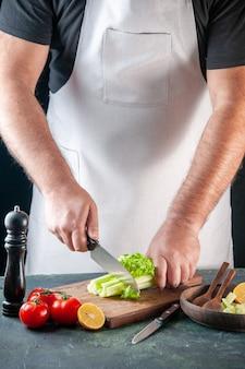 Вид спереди мужского повара, режущего сельдерей на темной стене, диетическое питание, фото, еда, здоровье, цвета