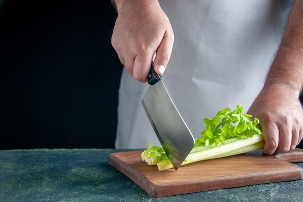 Вид спереди мужской повар, режущий сельдерей на темной стене, здоровье, диета, еда, цветная фотография, еда