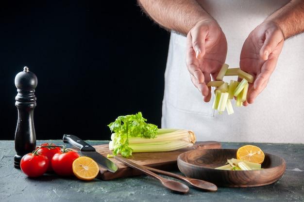 Вид спереди мужчина повар резка сельдерея на темной стене салат диетическая еда фото пищевые красители готовка кухня