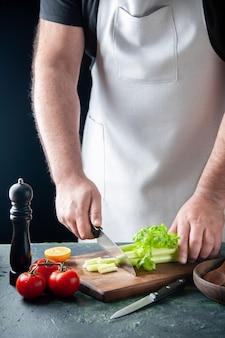 Вид спереди мужской повар, режущий сельдерей на темной стене, салат, диета, еда, фото, еда, здоровье