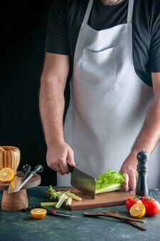 Вид спереди мужской повар, режущий сельдерей на темной стене, салат, здоровая диета, цветная фотография