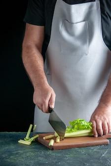 Вид спереди мужчина-повар, режущий сельдерей на темной стене, салат, здоровье, диета, еда, цвета, фото, еда