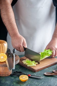 Вид спереди мужчина повар резка сельдерея на темном столе салат диета еда цвет фото еда здоровье
