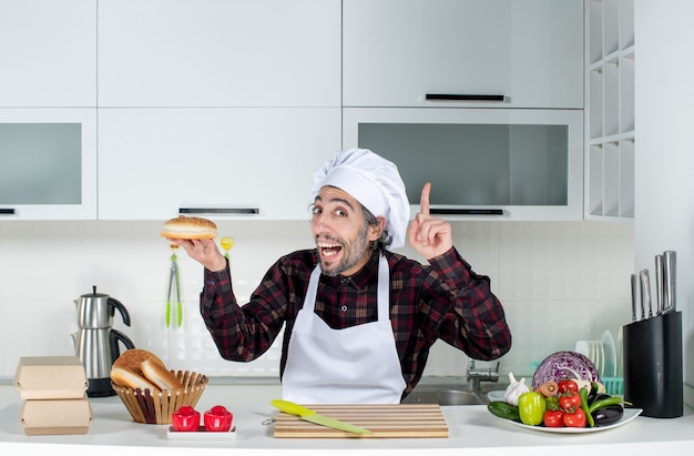 Front view of male cook holding bread surprising with an idea in the kitchen
