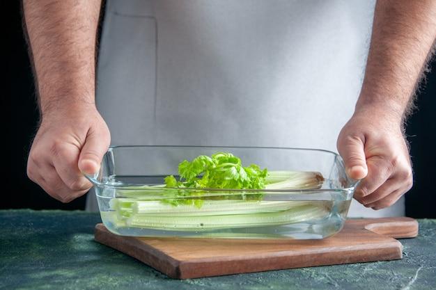 Вид спереди мужской повар, держащий тарелку с сельдереем на темной стене, салат, диета, еда, цветная фотография, здоровье, еда