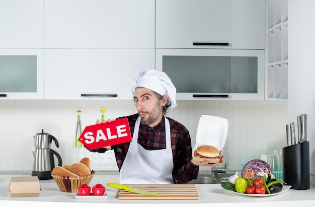 Front view of male cook holding up sale sign and burger in the kitchen