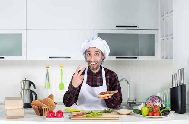 Front view of male cook making burger showing v gesture standing behind kitchen table
