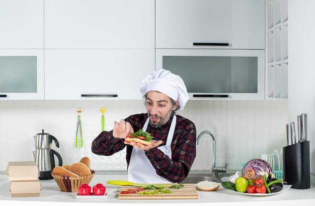 Vista frontale del cuoco maschio che prepara un delizioso hamburger in piedi dietro il tavolo della cucina