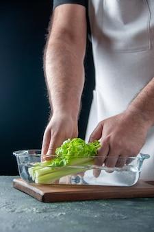 Vista frontale maschio cuoco tirando fuori il sedano dal piatto con acqua sulla parete scura insalata di dieta pasto foto a colori salute alimentare