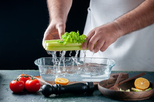 Вид спереди мужчина-повар вынимает сельдерей из тарелки с водой на темной стене салат диетическое питание фото еда здоровье цвет