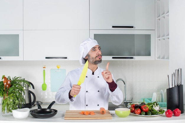 Front view male cook in uniform holding knife surprising with an idea in the kitchen