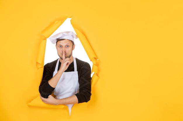 Front view male cook in white cape and cap on yellow ripped cuisine color job kitchen food man