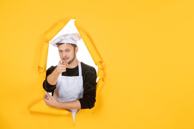 Front view male cook in white cape and cap on the yellow ripped cuisine color photo job kitchen food man