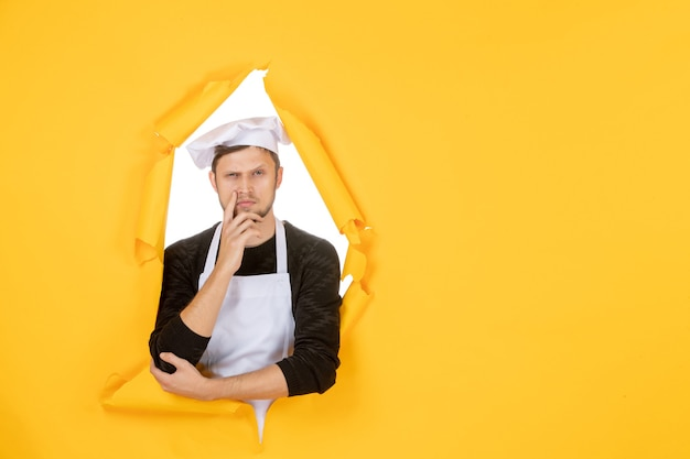 Front view male cook in white cape and cap on yellow ripped cuisine color photo job kitchen food man