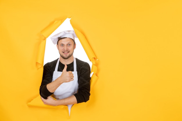 Front view male cook in white cape and cap on yellow ripped cuisine color photo job kitchen man