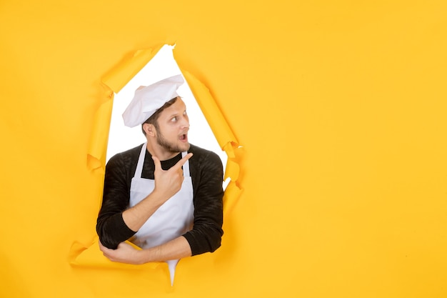 Front view male cook in white cape and cap on yellow ripped cuisine color photo kitchen food man