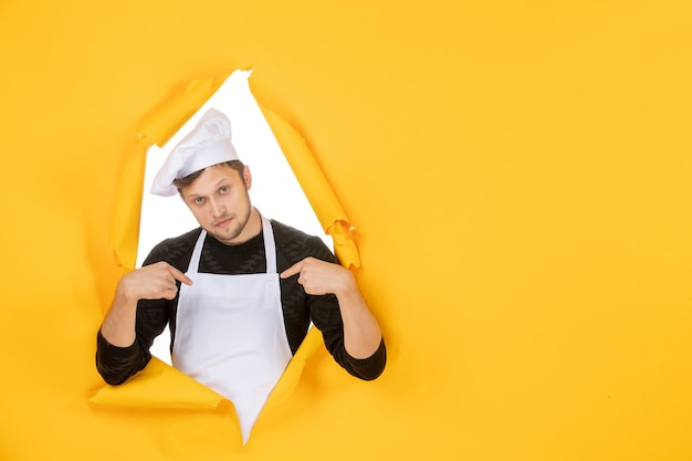 Front view male cook in white cape and cap on yellow ripped food job color kitchen man cuisine photo