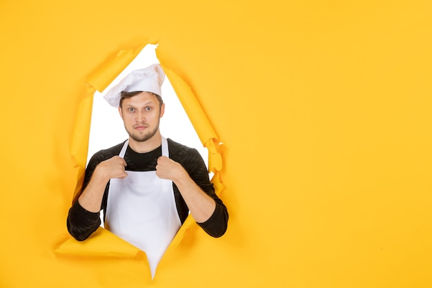 Front view male cook in white cape and cap on yellow ripped food job color white man cuisine photo