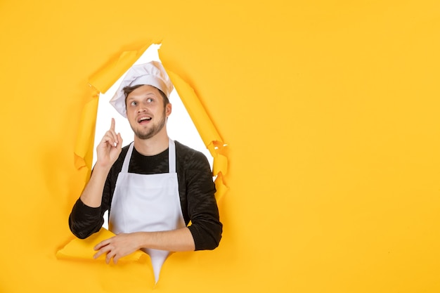 Front view male cook in white cape and cap on a yellow ripped food job white kitchen man cuisine photo color