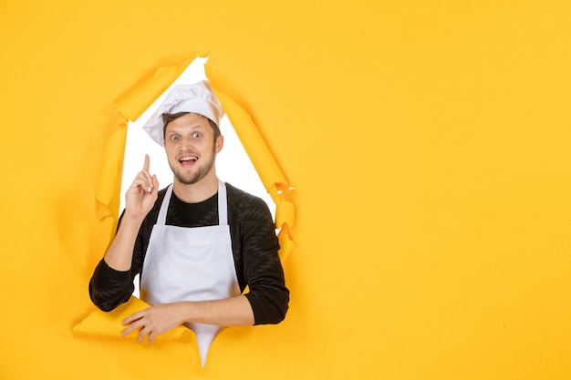 Front view male cook in white cape and cap on yellow ripped food job white kitchen man cuisine photo color