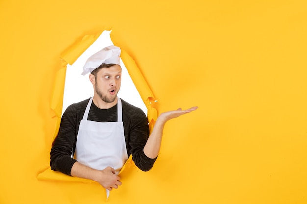 Front view male cook in white cape and cap on yellow ripped food job white kitchen man cuisine photo colors