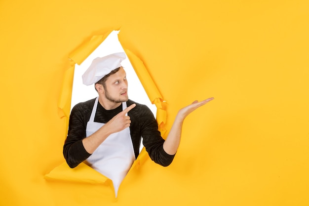 Front view male cook in white cape and cap on yellow ripped job color photo kitchen man cuisine