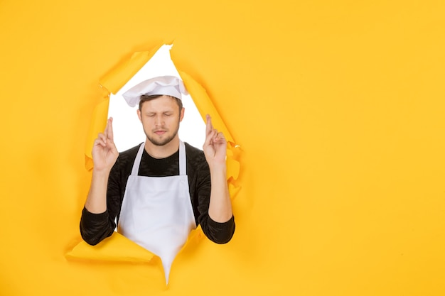 Front view male cook in white cape and cap on yellow ripped job color white photo food man cuisine