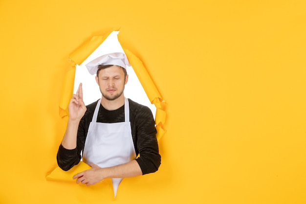 Front view male cook in white cape and cap on the yellow ripped job color white photo kitchen food man cuisine