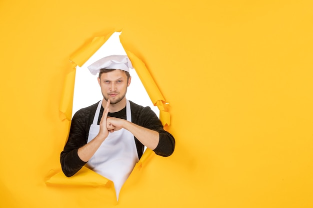 Front view male cook in white cape and cap on yellow ripped job color white photo kitchen food man cuisine