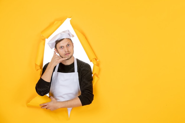 Front view male cook in white cape and cap on yellow ripped job color white photo kitchen man cuisine