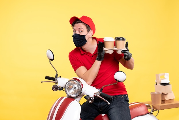 Front view male courier on bike in mask with coffee on a yellow