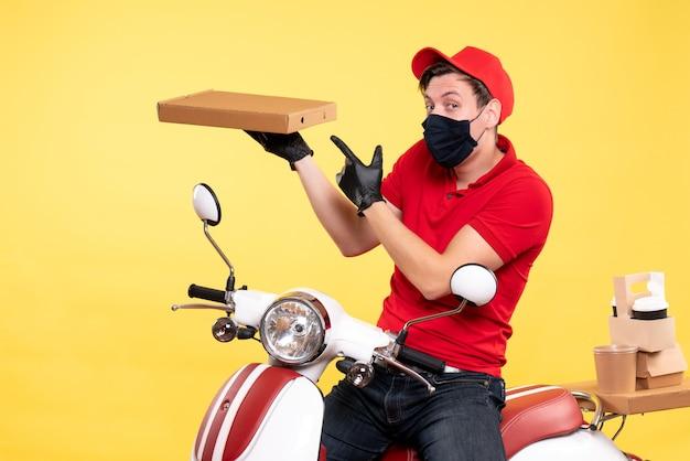 Corriere maschio vista frontale in bici in maschera con scatola per alimenti su giallo