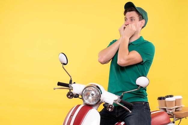 Corriere maschio vista frontale in bici con faccia spaventata su giallo