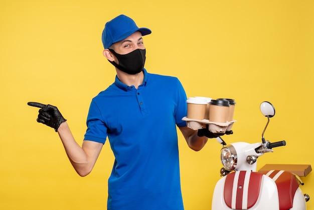 Corriere maschio di vista frontale nella maschera nera che tiene caffè sul lavoro di consegna giallo covid pandemia lavoro servizio uniforme