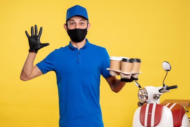 Corriere maschio di vista frontale nella maschera nera che tiene caffè sul servizio di lavoro di consegna covid- pandemia di lavoro giallo