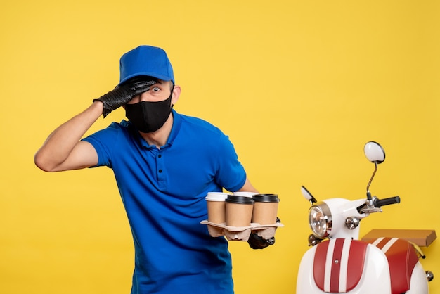 Corriere maschio di vista frontale nella maschera nera che tiene caffè sul lavoro di consegna del servizio di pandemia di lavoro giallo covid