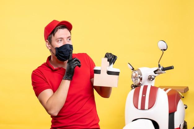 Corriere maschio vista frontale in maschera nera con tazze di caffè sul lavoro di consegna del lavoro di covid-servizio virus lavoratore giallo