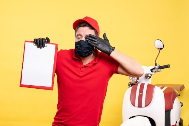 Corriere maschio vista frontale in maschera nera con nota di file sul virus del servizio di lavoro pandemico di consegna covid di lavoro giallo