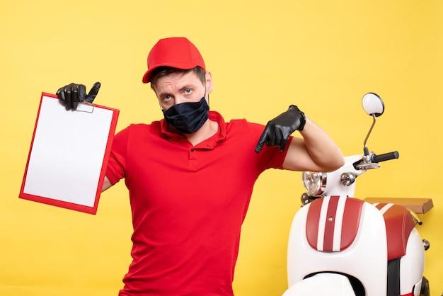 Corriere maschio vista frontale in maschera nera con nota di file sul virus del servizio di lavoro pandemico di consegna covid uniforme gialla