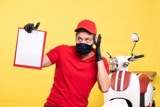 Corriere maschio vista frontale in maschera nera con nota di file sul lavoro uniforme gialla virus del servizio pandemico di consegna covid