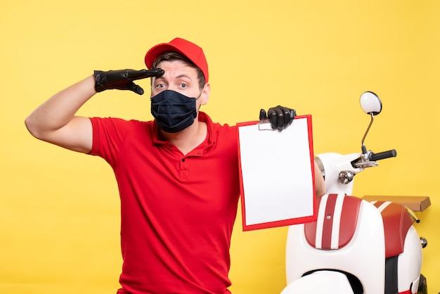 Corriere maschio vista frontale in maschera nera con nota di file su lavoro uniforme gialla consegna covid virus servizio di lavoro pandemico